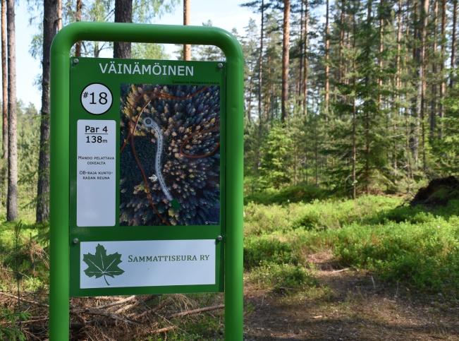 metsässä kyltti, jossa lukee Väinämöinen ja Sammattiseura ry