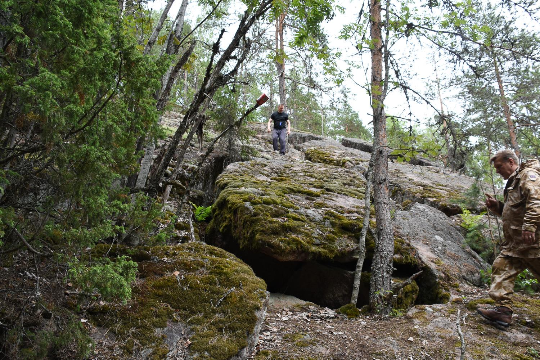 kaksi miestä jyrkällä kalliorinteellä