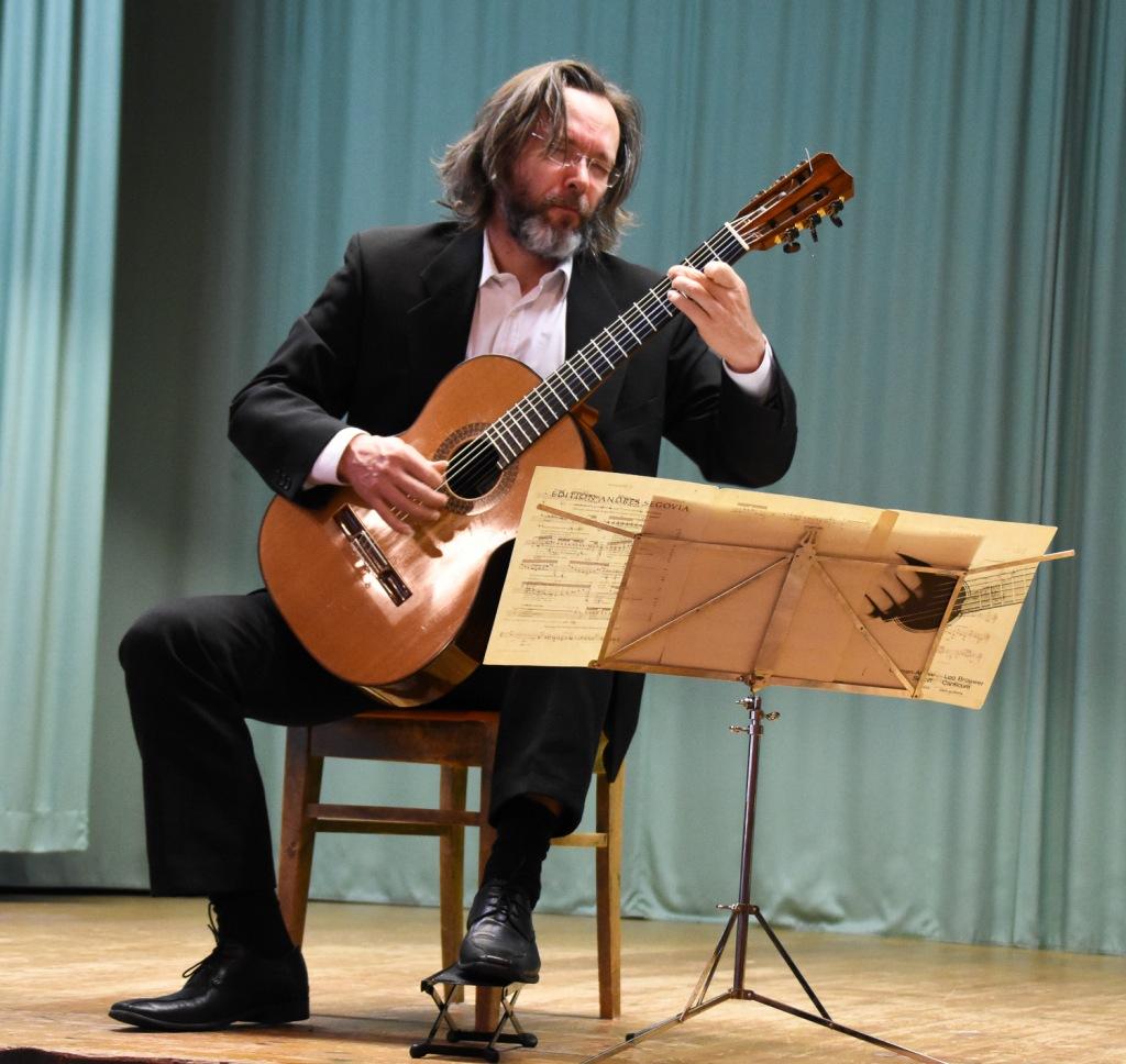 Mies soittaa istuallaan kitaraa. Hänen edessään on nuottiteline.