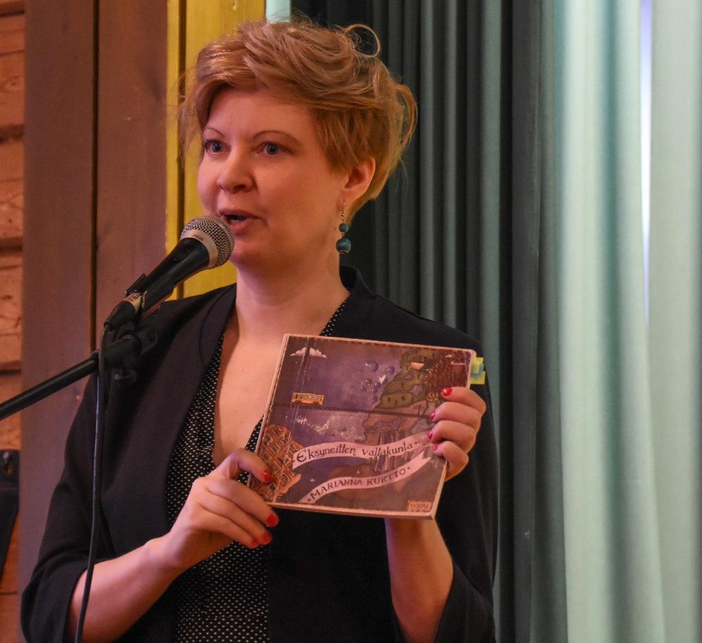 Nainen mikrofonin ääressä, pitää kädessään kirjaa, jonka kannessa lukee Marianna Kurtto Eksyneitten valtakunta.
